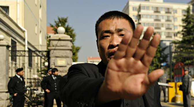 Unfree speech … a plain-clothes policeman tries to stop photos being taken outside the house of Liu Xia. Photograph: Peter Parks/AFP/Getty Images